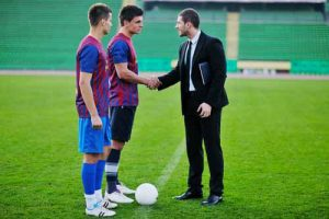 An athlete agent shakes hands with a soccer player.