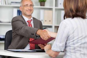 A man shakes hands with a client.