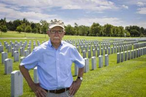 A veteran stands in front of a cemetery.
