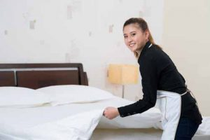 A housekeeper makes up a bed.