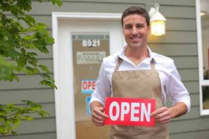 "A business owner holds an ""open"" sign."