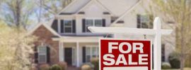 """A """"for sale"""" sign is in front of a house."""
