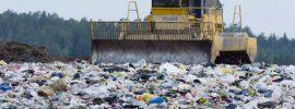 A bulldozer moves trash in a landfill.