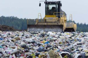 A bulldozer moves trash in a landfill.